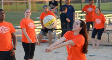 team playing sand volleyball